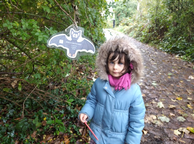 child in coat by bat sign with pencil