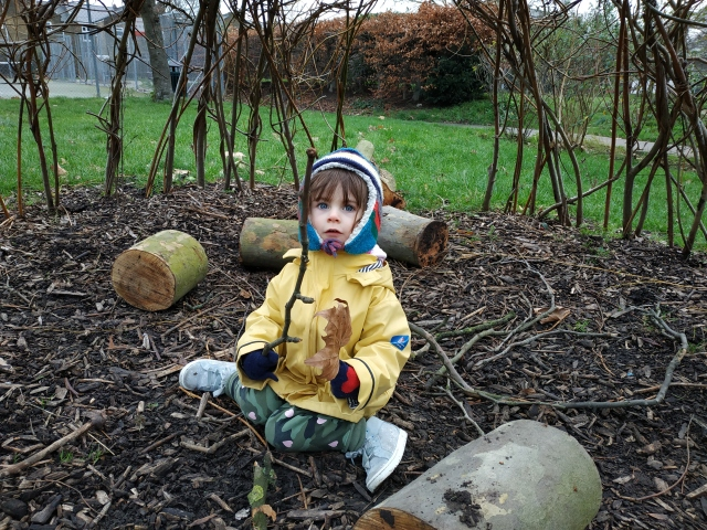 child holding stick in willow wigwam