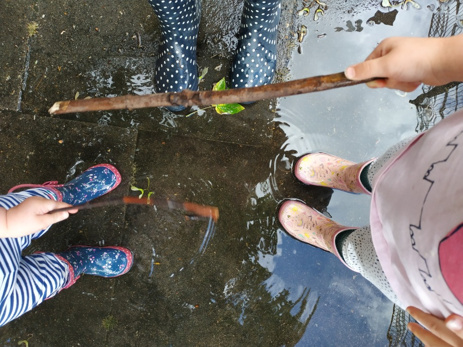 three pairs of feet wearing wellies in a puddle