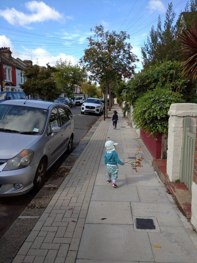 children walking down a road carrying sticks