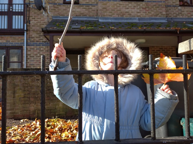 child holds a stick and a leaf behind railings