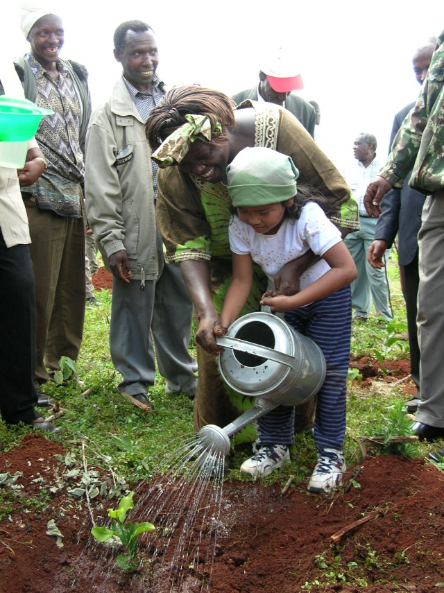 Child watering a tree seedling with adults watching