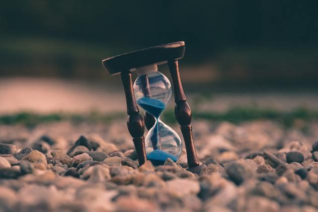 hourglass on pebble shore