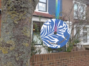 pretty sign hanging from rowan tree outside house