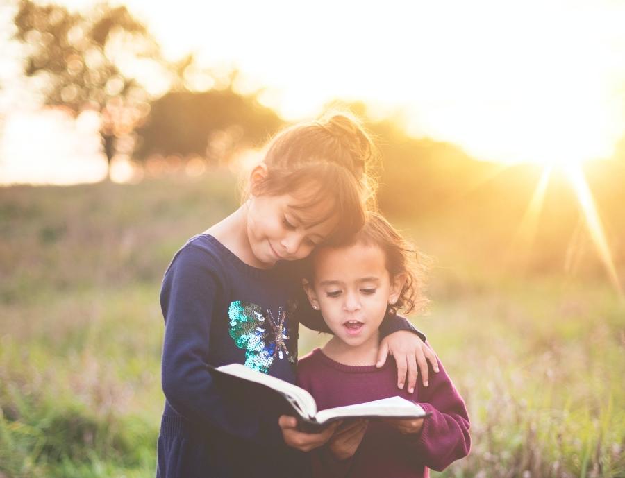 children reading a book in a field