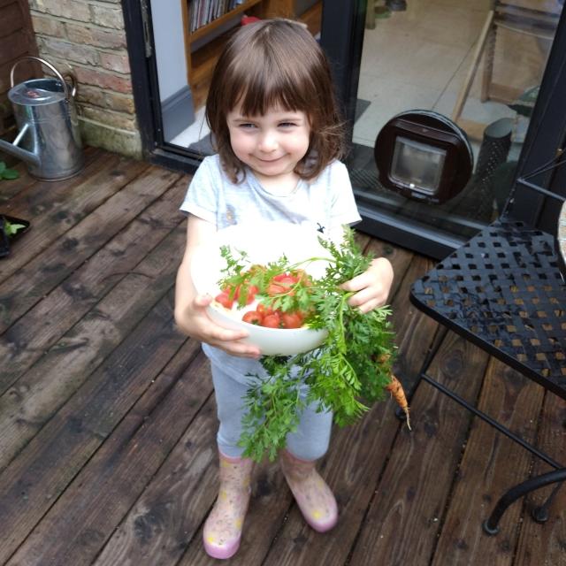little girl holding home grown vegetables